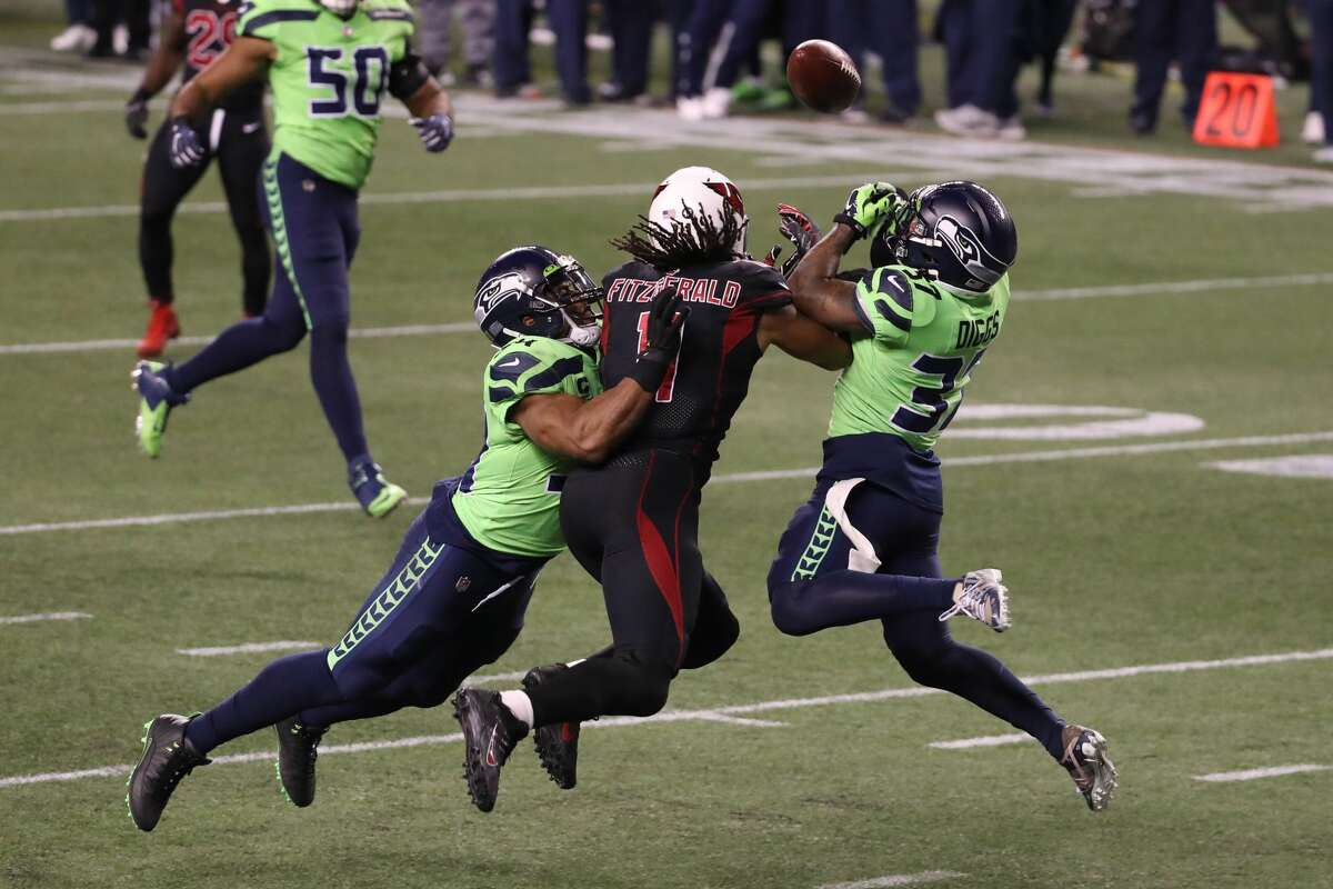 SEATTLE, WASHINGTON - NOVEMBER 19: Larry Fitzgerald #11 of the Arizona Cardinals has his pass broken up by Quandre Diggs #37 and Bobby Wagner #54 of the Seattle Seahawks in the fourth quarter at Lumen Field on November 19, 2020 in Seattle, Washington. (Photo by Abbie Parr/Getty Images)