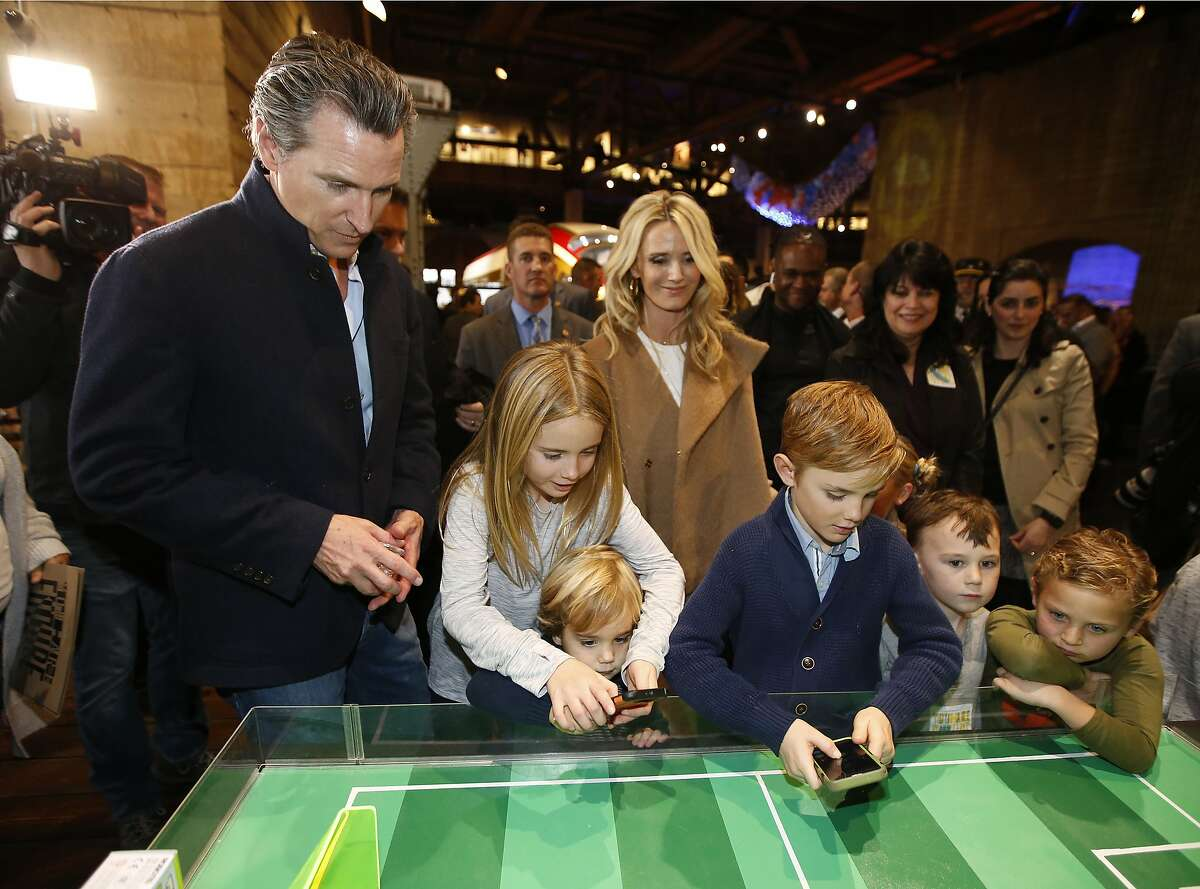 Then-Lt. Gov. Gavin Newsom and wife Siebel Newsom watch their children, daughter Montana, second from left, and sons, Dutch, foreground, and Hunter, foreground fourth from left, operate robot games at the California Railroad Museum, Sacramento, Calif. Newsom said Friday, Oct. 30, 2020, his children are among those resuming in-person classes after months of distance learning due to the coronavirus pandemic. (AP Photo/Rich Pedroncelli, File)