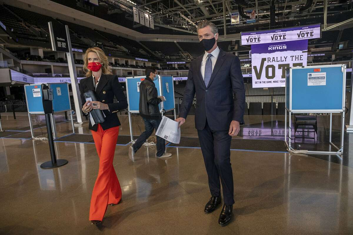 California Gov. Gavin Newsom, right, and his wife Jennifer Siebel Newsom leave the voting booth to drop of their tickets after voting under COVID-19 protocols at Golden 1 Center in Sacramento, Calif., Thursday, Oct. 29, 2020. (Renée C. Byer/The Sacramento Bee via AP, Pool)