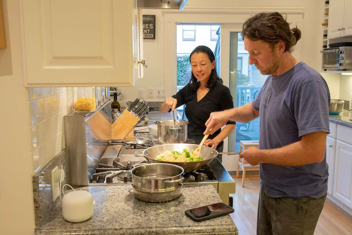 Karen Cheng and her spouse Peter make dinner, Saturday, Nov. 21, 2020, in San Francisco, Calif. Cheng is a co-owner of Star Anise Foods, which makes plant-based Vietnamese food products. During the pandemic, she's seen her own family's eating habits change, as well as watching consumer behavior changing as a food professional.