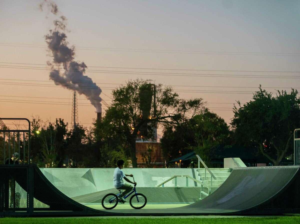 A child rides a bike at a skate park near the ExxonMobil facility, Wednesday, Nov. 11, 2020, in Baytown.