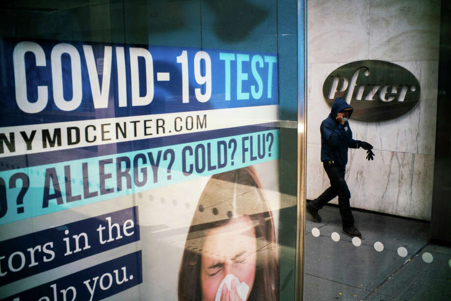 A man walks in front of Pfizer headquarters. The drug maker company Pfizer says its COVID-19 vaccine is 95%, which is providing promise in the pandemic fight. But doctors across west-central Illinois still are trying to understand more fully the long-term effects the illness brings to some people. Photo: VIEW Press / 2020 VIEWpress