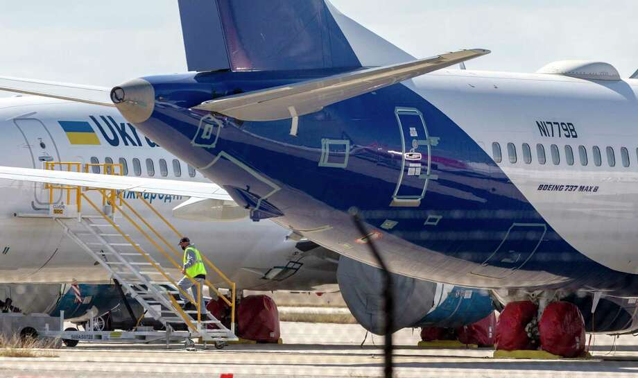 A person climbs a ladder to a Boeing 737 Max aircraft sitting Wednesday, Nov. 18, 2020 on the tarmac at Port San Antonio the day the FAA approved the plane, which was grounded worldwide on March 13, 2019, to return to flight. The majority of the 737 Max aircraft in San Antonio are new aircraft that have yet to be delivered to their owners. Photo: William Luther /Staff Photogra / ©2020 San Antonio Express-News