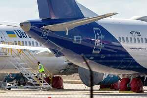 A person climbs a ladder to a Boeing 737 Max aircraft sitting Wednesday, Nov. 18, 2020 on the tarmac at Port San Antonio the day the FAA approved the plane, which was grounded worldwide on March 13, 2019, to return to flight. The majority of the 737 Max aircraft in San Antonio are new aircraft that have yet to be delivered to their owners.
