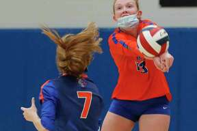In this file photo, Grand Oaks outside hitter Mykenah Calder (13) makes a save in front of libero Ava Terry (7). The Grizzlies saw their season end in an area round sweep against top-ranked Klein on Nov. 23, 2020.