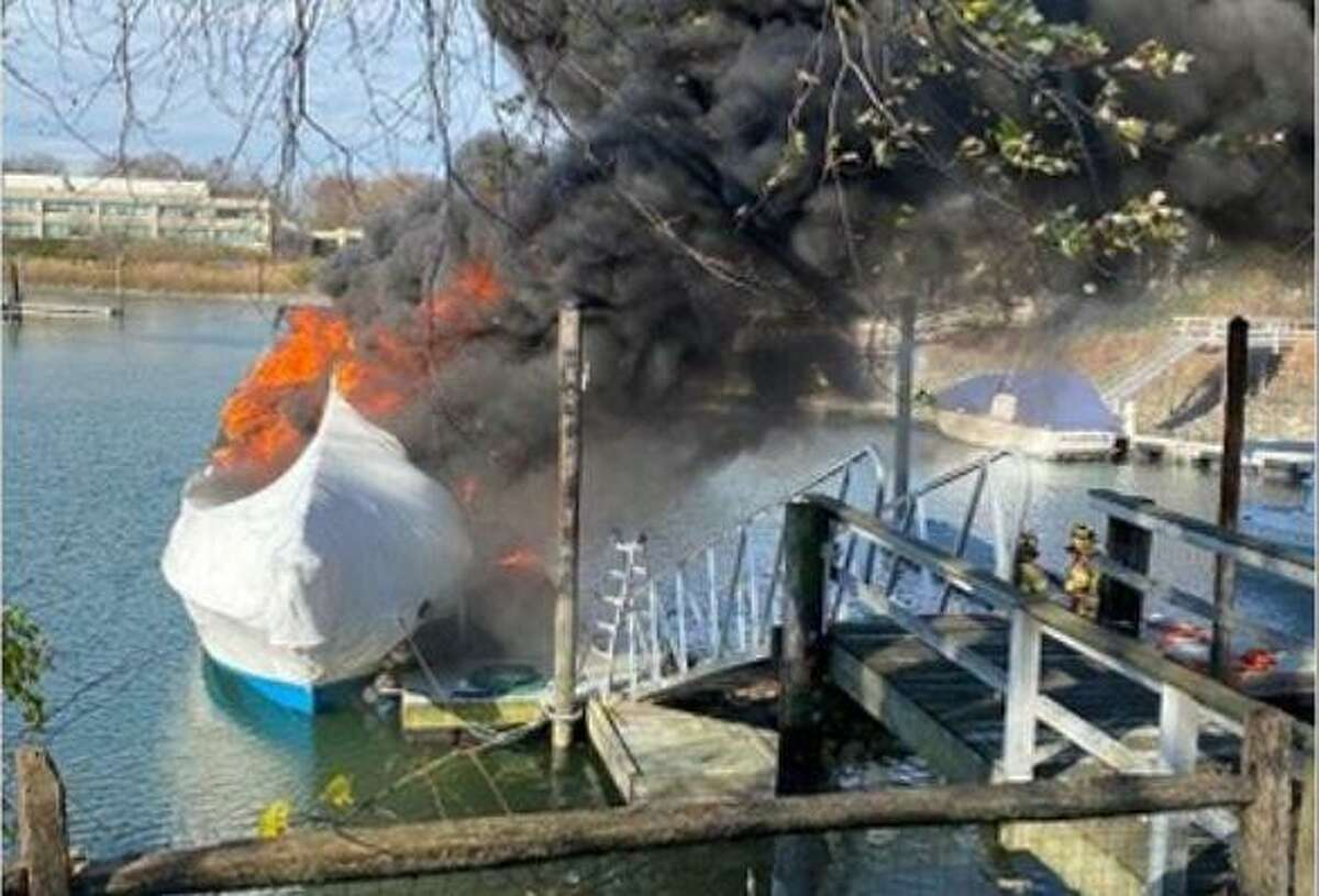 Fire officials respond to a boat fire at Dolphin Cove on Saturday afternoon. Stamford's Chief Fire Marshal Walter Seeley said the blaze, which was reported by numerous Dolphin Cove Quay neighbors just after noon on Saturday, has been ruled an accident. The fire was set by workers while they were shrink-wrapping the vessel, Seeley said. For decades, boat owners have used white plastic shrink wrap to keep water and snow as well as wildlife out of boats while they are in storage for the winter. To apply it, a wood frame is constructed over the vessel and the white plastic wrap is applied on top of the frame and then shrunk into place by using propane torches or heat guns.