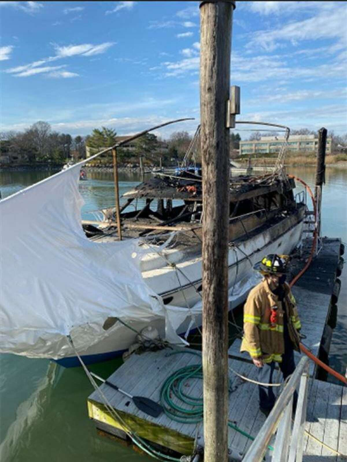 Fire officials respond to a boat fire at Dolphin Cove on Saturday afternoon. The fire on Dolphin Cove Quay was accidentally set when the torch ignited the shrink wrap and the burning plastic dripped onto the boat, setting it ablaze, Seeley said. Workers told firefighters that they had just finished the left side of the boat, and were applying heat to the right side of the boat, from a small boat, when they saw flames and smoke coming from the left side, Deputy Fire Chief Matt Palmer said. Firefighters arrived within three of the call and quickly extinguished the blaz before the 1988 vessel, manufactured by Silverton, could sink, Palmer said. As a result of the efforts of thee 22 responding firefighters, Palmer said there was no environmental damage to the cove. No injuries were reported.