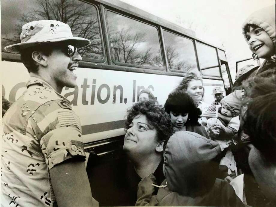 In this photo dated May 1, 1991, Sgt. Laurance Robert Flemming Jr. is greeted with a mix of adoration and happiness by his family - wife, Lauri; Amanda, 4, far right, and Robert, 1, bottom with back to the camera. (Daily News file photo)