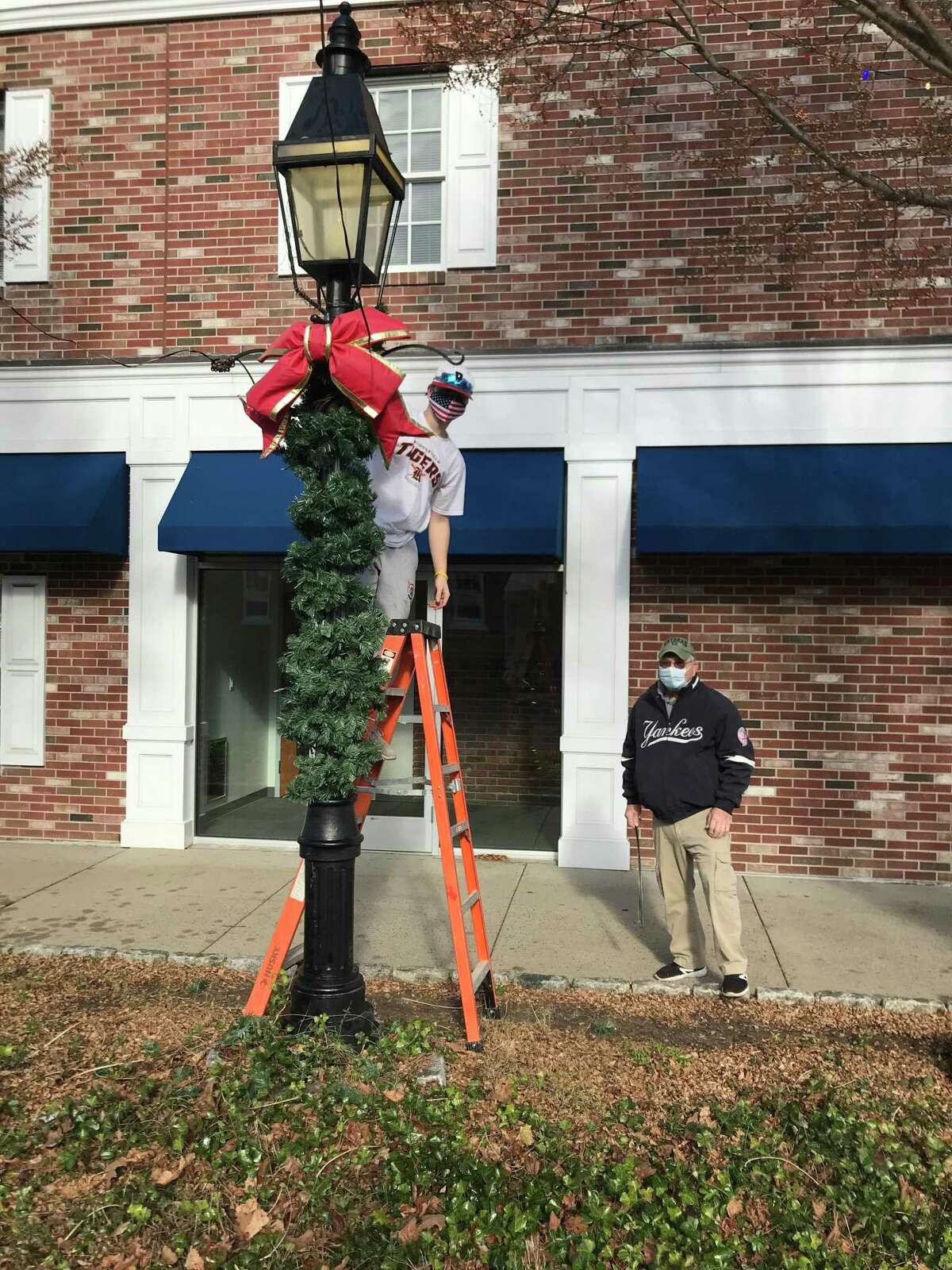 American Legion Post 78 in Ridgefield Legionnaire Mike Liberta and Legionnaire Bridger Rowan decorate a lamppost near a brick building on Catoonah Street in the town on Saturday, Nov. 21 as part of their annual decorating of lampposts in the town.