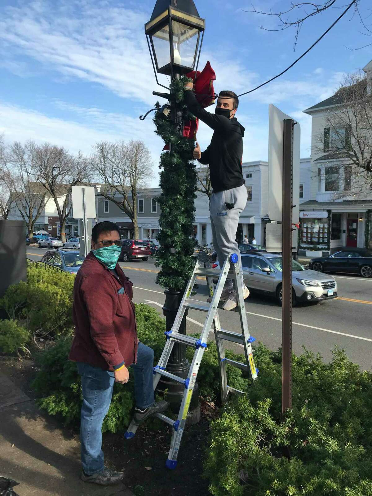 American Legion Post 78 in Ridgefield Legionnaire Steve Barrientos and Legionnaire Andrew Filippelli decorate a lamppost on Main Street in the town on Saturday, Nov. 21 as part of their annual decorating of lampposts in the town.