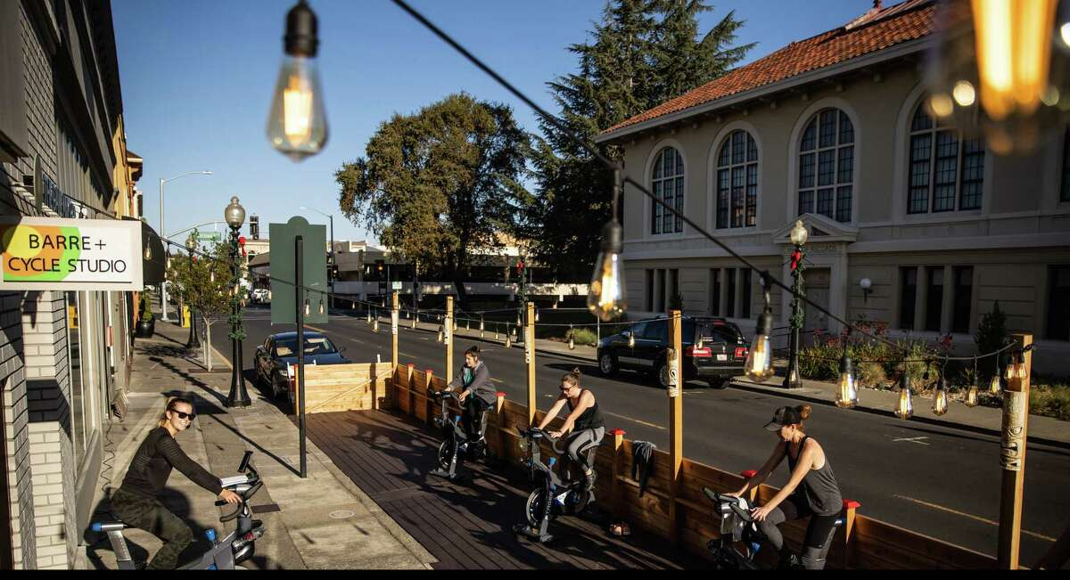 Sam Mills, left, leads an outdoor spin class on parking spaces converted to a parklet for local businesses like The Dailey Method in Napa, Calif.