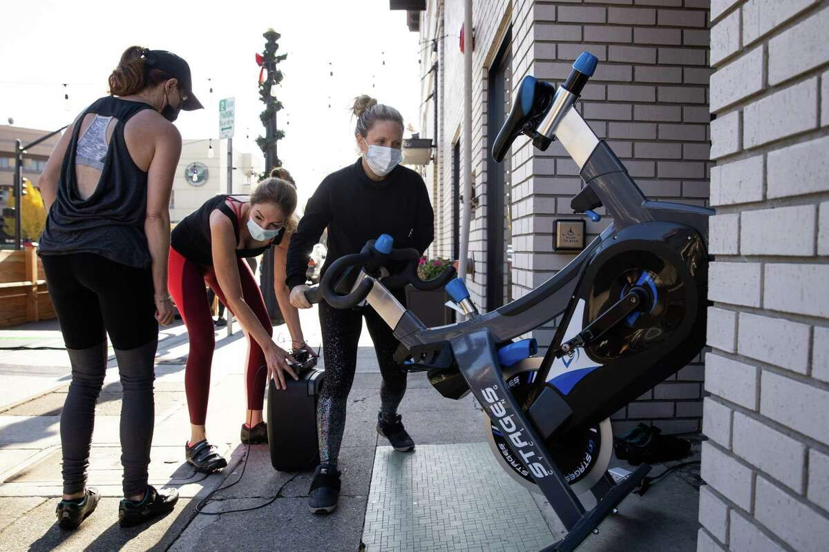 The Dailey Method owner Kelli Stuart wheels stationary bikes inside as they switch from a spin class to barre in Napa, Calif.