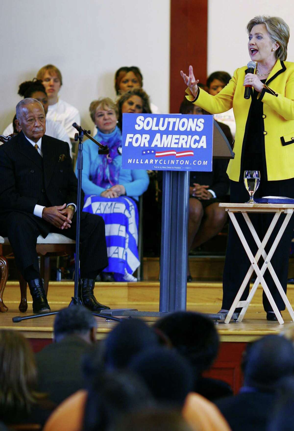 Former New York Mayor David Dinkins, seated at left, listens to New York Sen. Hillary Clinton, 2008 Democratic presidential hopeful, speak at Benedict College in Columbia, S.C., on Jan. 25, 2008.