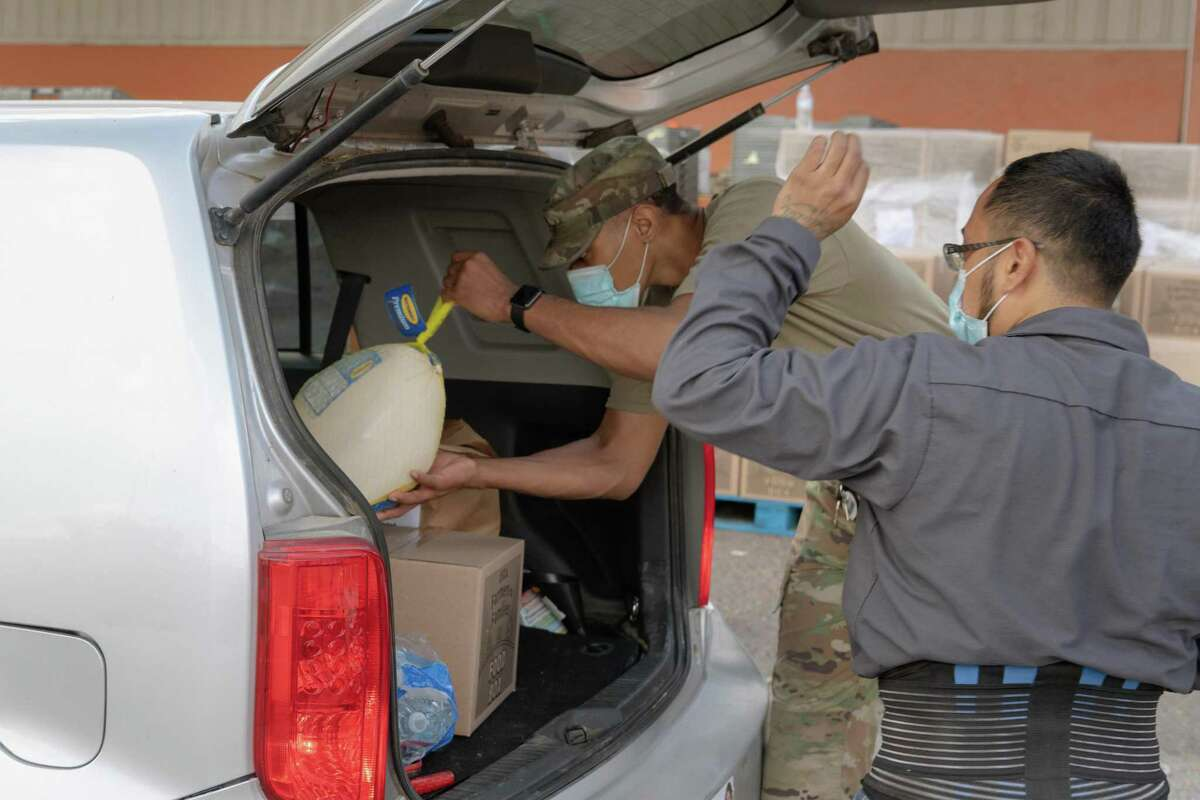 South Texas Food Bank staff and members of the Army National Guard load hundreds of cars with the makings of a Thanksgiving Dinner on Monday.