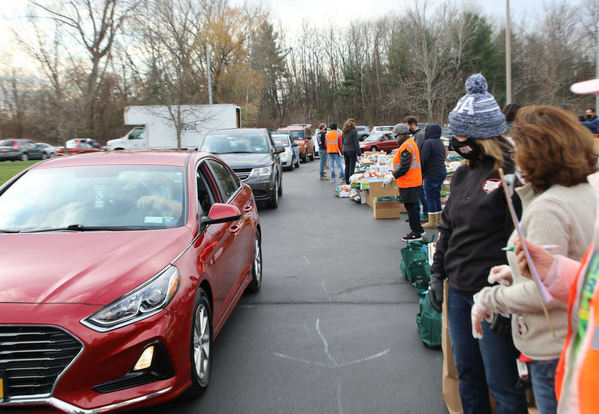 Capital Region residents line up in their vehicles to receive food as part of a drive-thru food pantry at the New York State United Teachers union's headquarters in Latham on Friday. Working in partnership with the Regional Food Bank of Northeastern New York, Catholic Charities and the Capital District Area Labor Federation, the union had enough food on hand to feed 900 families. A portion of the food - which included a variety of fresh fruit and vegetables, meat, dairy products and shelf-stable foods - was made available specifically for members of the Albany Public School Teachers Association, Albany Public School United Employees and Schenectady Federation of Teachers who were laid off earlier this year.