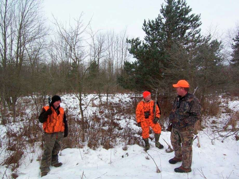 Hunters compare notes at the end of a late-season deer drive. (Photo provided/Tom Lounsbury/Hearst Michigan)