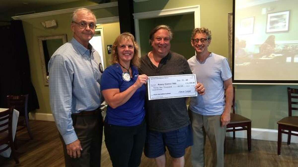From left, Tad Smith, Carrie Reed, Steve Cooper, and Gary Opin displaying a check for $32,000 made at an Arlo Guthrie concert at the Milford Performance Center for Rotary International. This money was tripled by Bill Gates, making it $96,000 towards polio prevention.