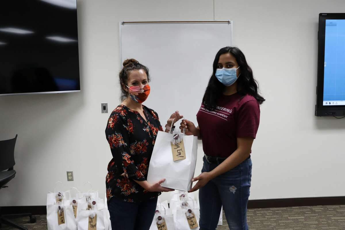 """Shea Thompson, president, Midland Aggie Moms Club, presents """"gig 'em"""" final exam gift to Evelyn Abendroth. a student at Texas A&M University-Concho Engineering Academy at Midland College."""