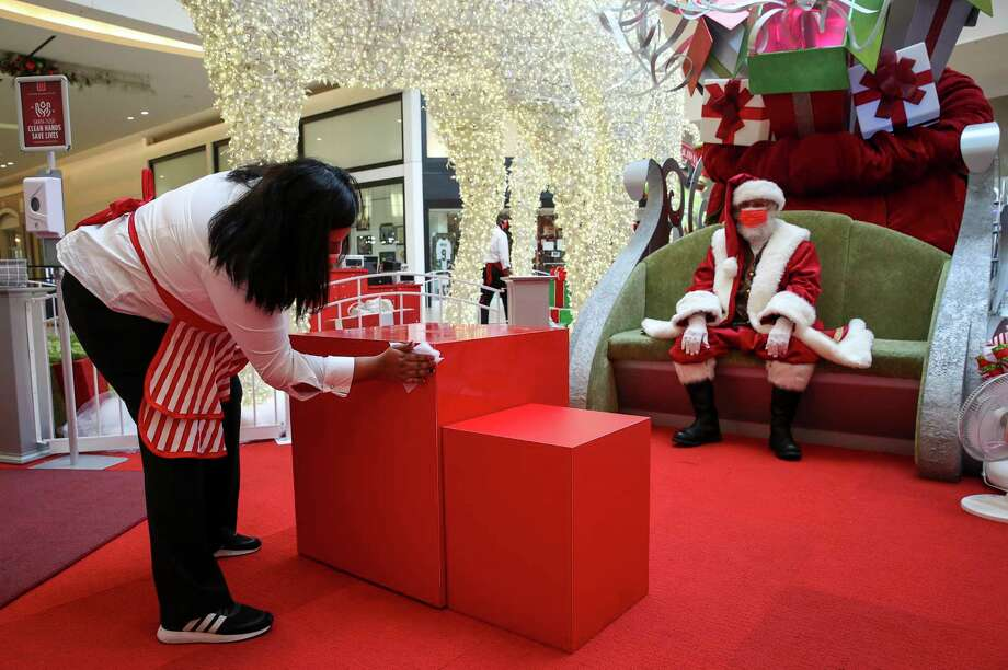 """Maria Salvador cleans a seat after two children posed for a socially-distant photo while Santa (aka Boaz Arch), waits at Memorial City Mall. Arch, who is 70, said he is a diamond cutter by trade, and that he performs as Santa a few months each year. """"In the jewelry business, it's all about the joy,"""" he said. """"So I wanted to continue that tradition."""" Photo: Jon Shapley Houston Chronicle Staff Photographer / © 2020 Houston Chronicle"""