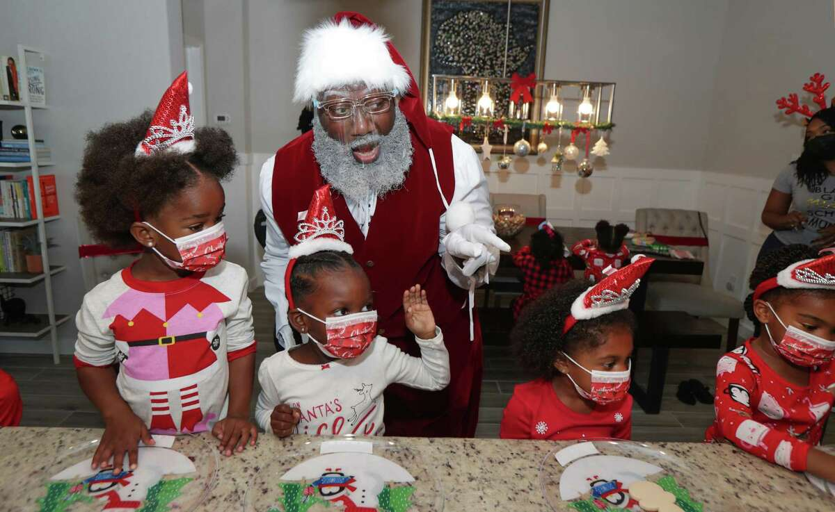 Urennaya Unaka (l-r), Chandler Palmer, Santa (aka Kelvin Douglas), of Black Santa Houston, Paetyn Jackson and Avery Mclenan work on craft projects at the Black Girl Magic School.