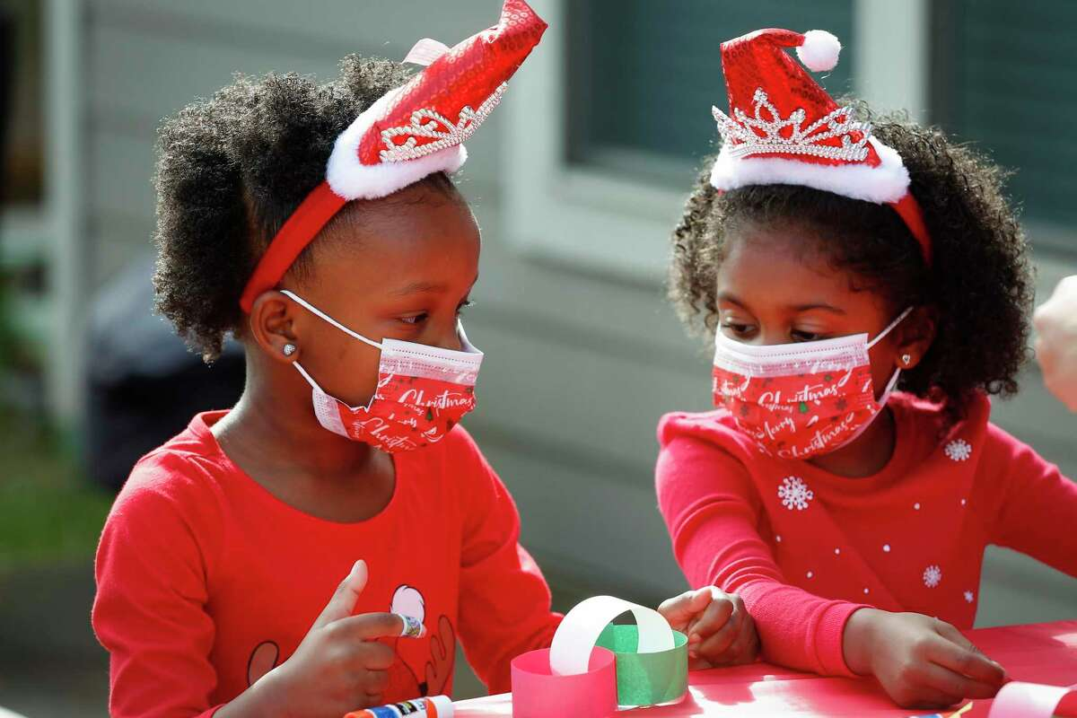 Auri Bentley and Paetyn Jackson work on a craft project at the Black Girl Magic School during Santa's visit.