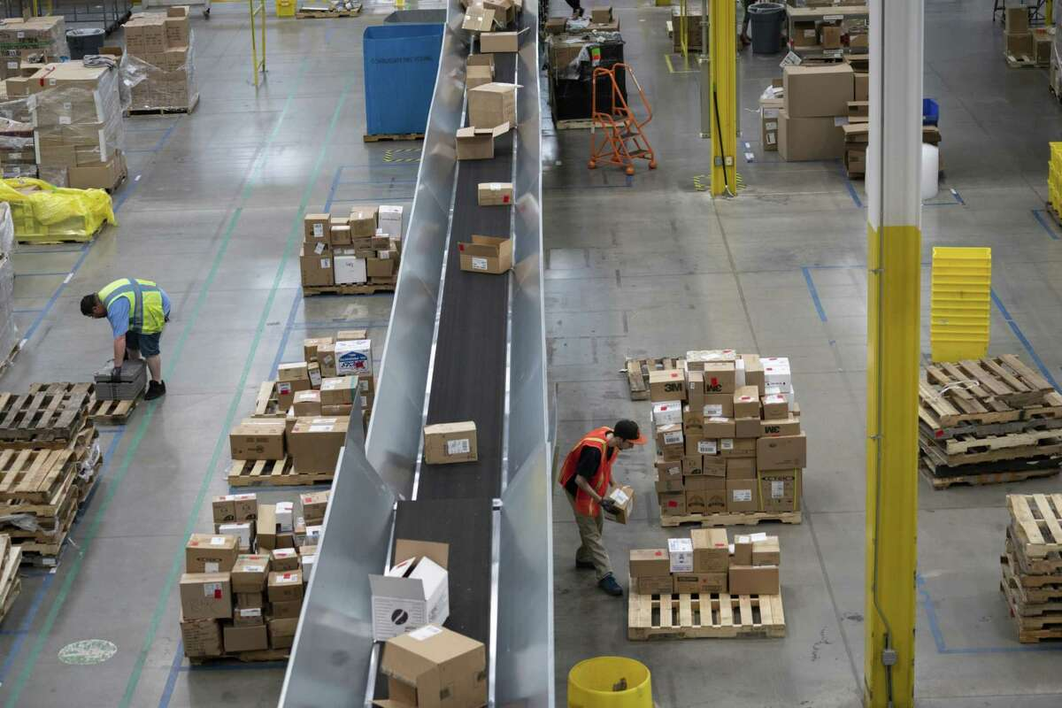 Employees work at an Amazon fulfillment center in Baltimore in 2019.