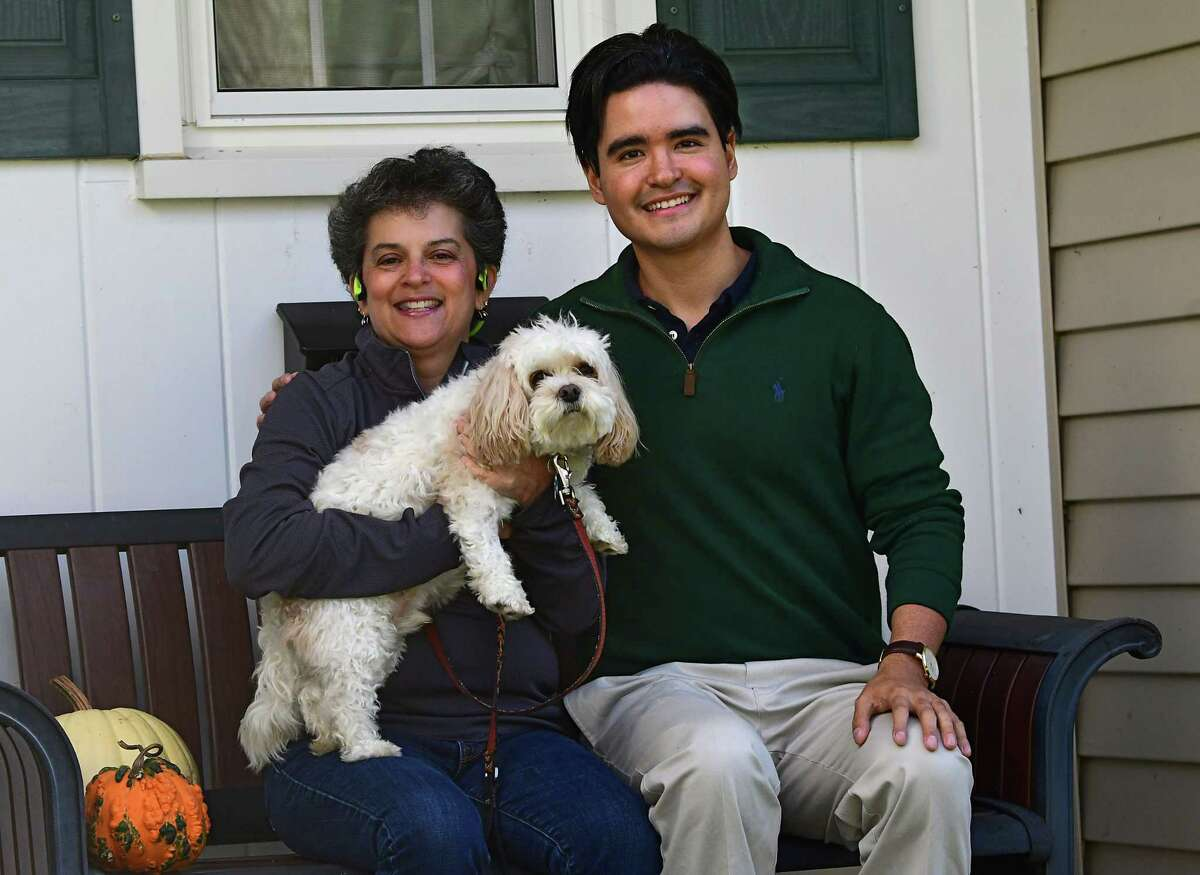 Lynell Engelmyer, holding her dog Bailey, sits next to Santiago Potes who learned over the weekend that he had received the prestigious Rhodes Scholarship on Tuesday, Nov. 24, 2020 in Niskayuna, N.Y. Potes has been staying with the Engelmyer family in Niskayuna for the past few months. (Lori Van Buren/Times Union)