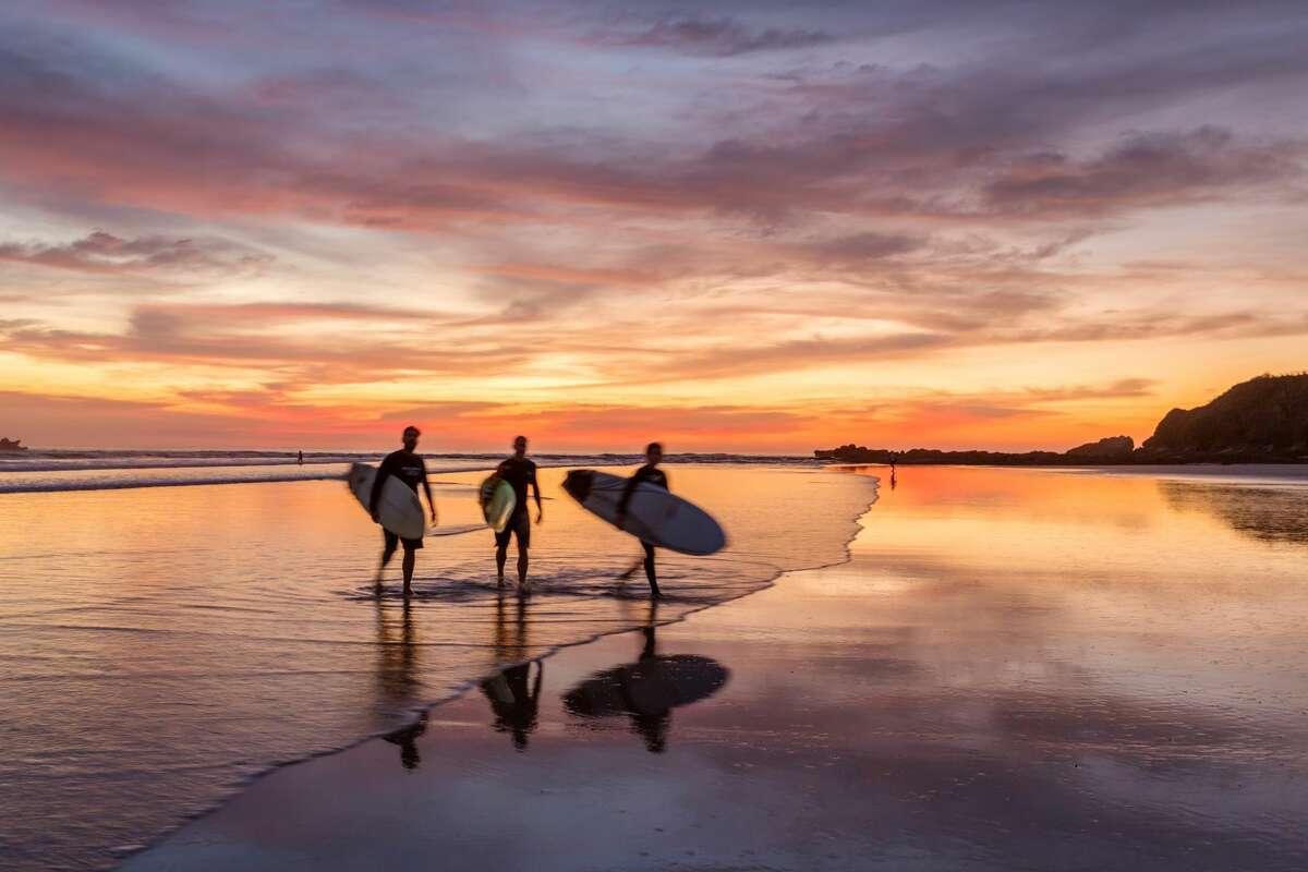 Surfers at sunset walking on beach, Playa Guiones, Nosara, Guanacaste, Costa Rica