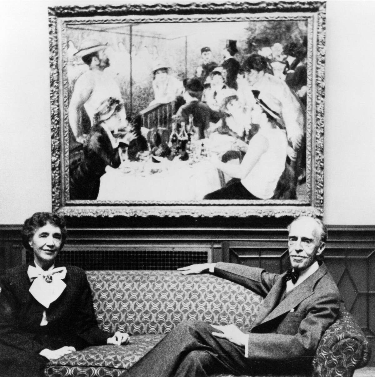 """Marjorie and Duncan Phillips, in about 1954, pose in front of Renoir's """"Luncheon of the Boating Party"""" (1880-81)."""
