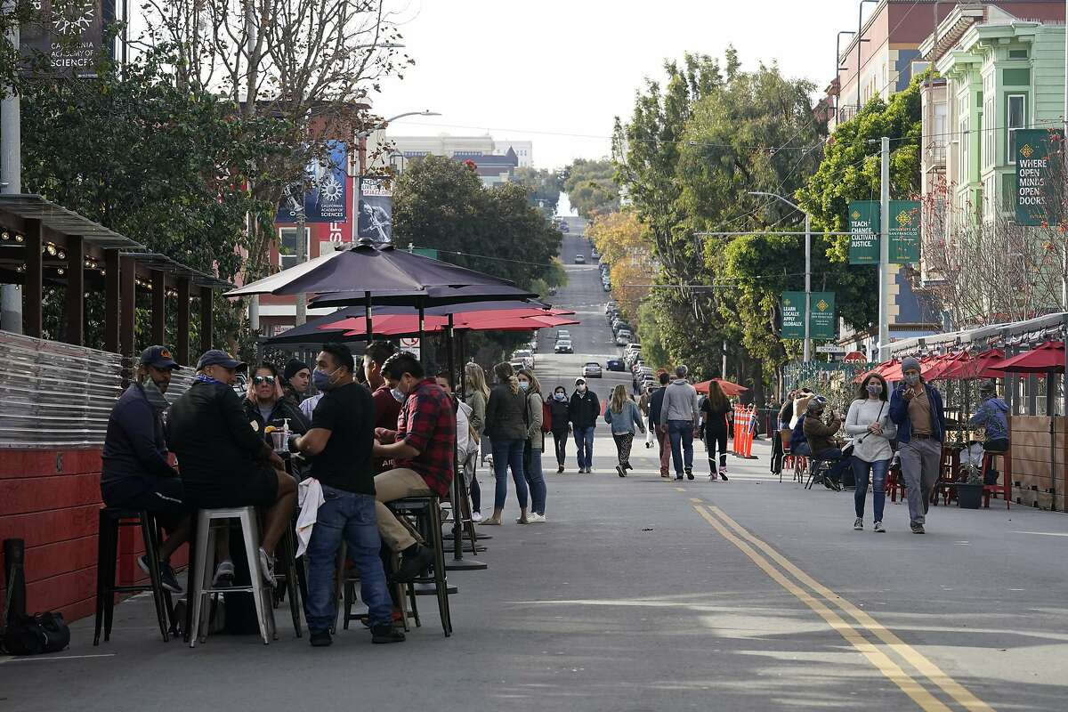 People sit in outdoor dining areas on Hayes street during the coronavirus outbreak in San Francisco, Saturday, Nov. 21, 2020. (AP Photo/Jeff Chiu)