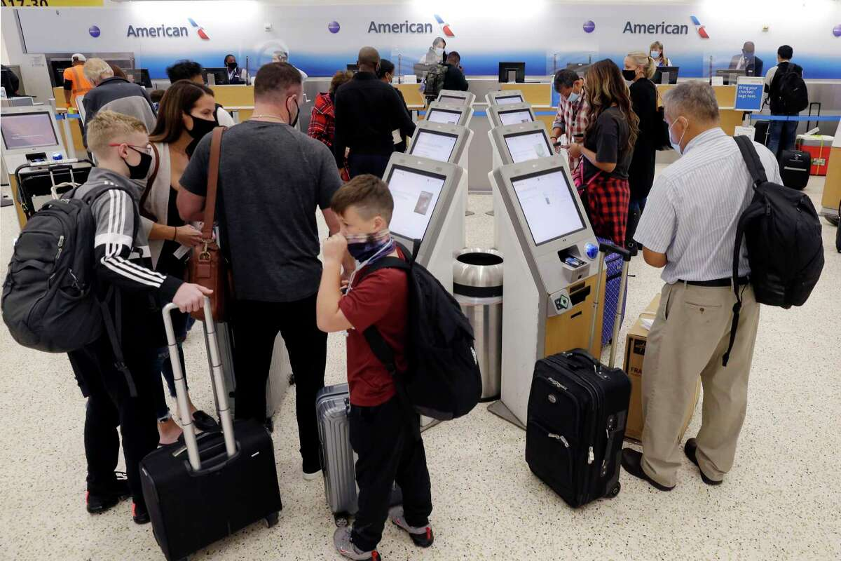 Travelers line up for check in at the ticketing machines at the American Airlines counter in Terminal A during the Thanksgiving holiday travel spike at IAH Tuesday, Nov. 24, 2020 in Houston.
