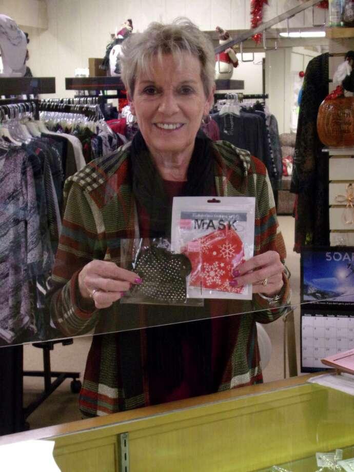 Darlene Schelkeshows offone of the masksfor sale in her Harbor Beach shop, Darlene's Fashions. (Rich Harp/For the Tribune)