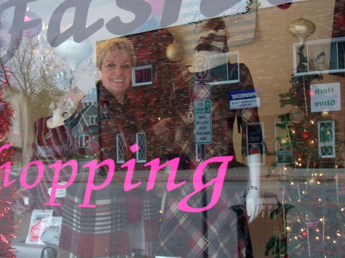 Darlene Schelkeposes for a photo in the window ofher Harbor Beach shop, Darlene's Fashions. (Rich Harp/For the Tribune)
