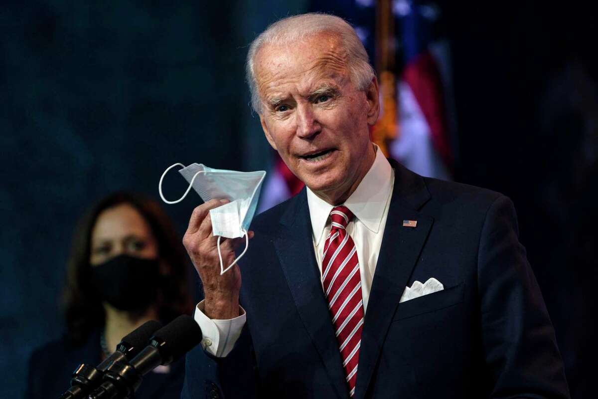 President-elect Joe Biden displays his face mask as he speaks about the coronavirus pandemic and economy in Wilmington, Del., on Nov. 16. Biden warned that a
