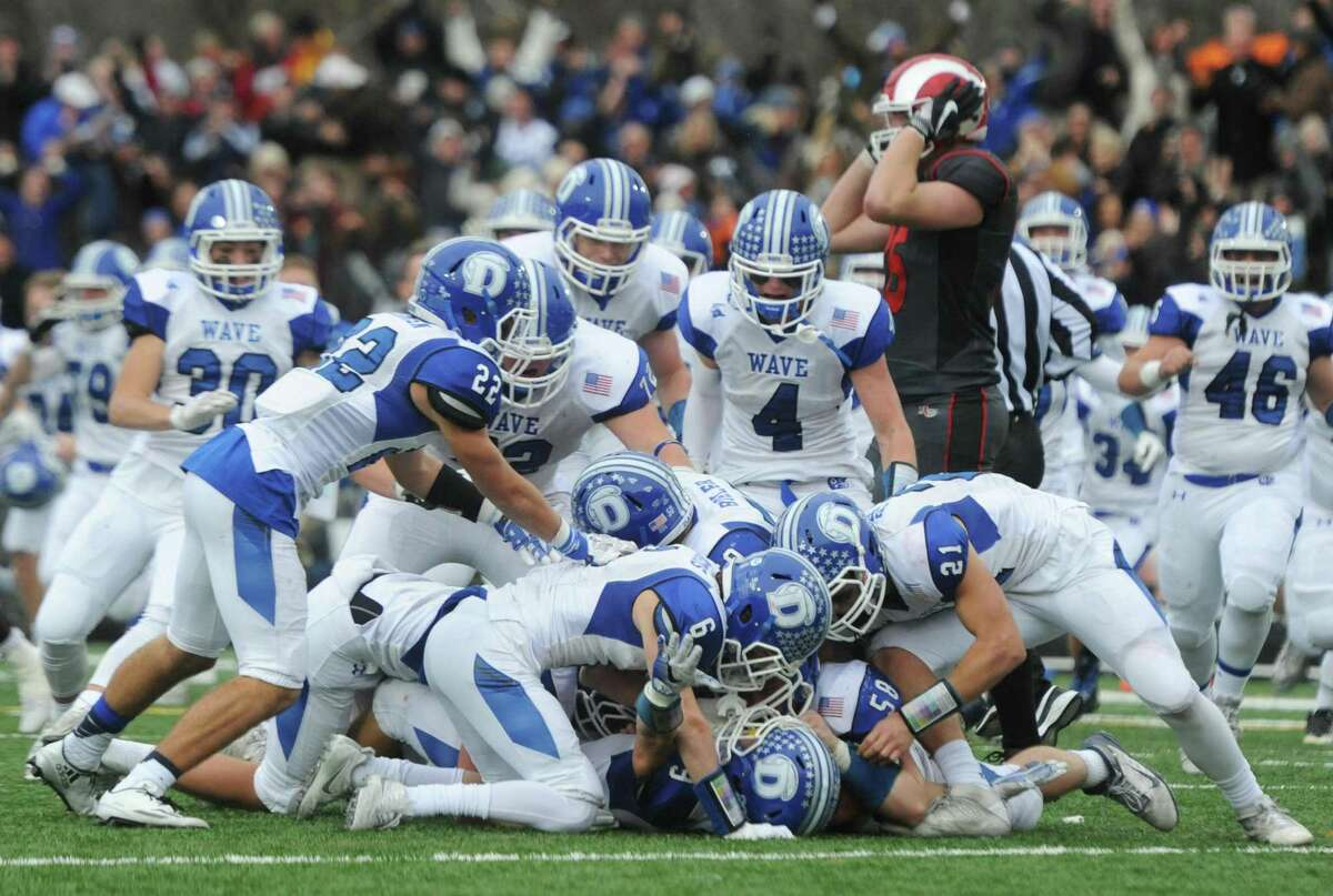 Darien players pile on top of one another after an overtime interception to win the game in Darien's 37-34 win over New Canaan in the Turkey Bowl football game in 2016. New Canaan scored 24 unanswered points to tie the game and force an overtime. In overtime, Darien kicked a field goal to take the lead and forced a New Canaan interception to end the game, setting off a wild celebration as fans stormed the field.