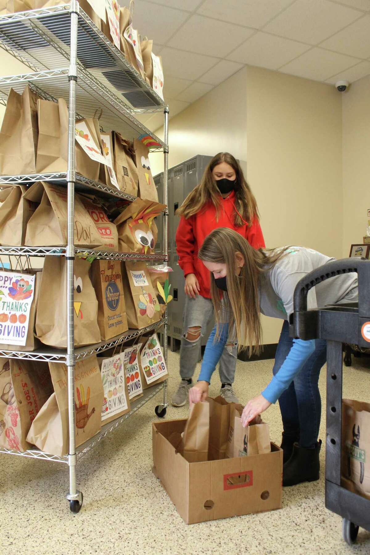 This year, Meals on Wheels Montgomery County will be delivering 692 meal bags to clients on Thanksgiving. Rylan and Misti Burgess, volunteers with the National Charity League Montgomery Monarchs, sort the Thanksgiving meal bags on Nov. 24, 2020.