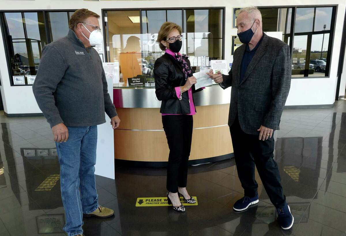 Norma Sampson accepts a donation of $13, 750 to the Gift of Life from Philpott motors' Daren. Granger (left) and Robert Thewman Monday at the Philpott Ford dealership in Nederland. Philpott has been a supporting partner of the program for 15 years, offering critical community support for the Gift of Life's health and wellness programs. Philpott donated $50 of every car sold through the month of Octoer to raise this year's donation. Photo taken Monday, November 23, 2020 Kim Brent/The Enterprise
