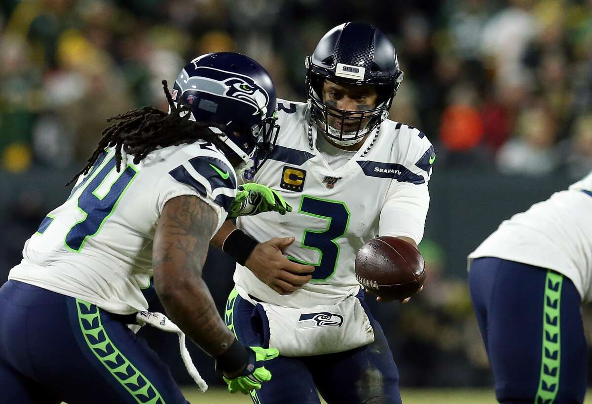 GREEN BAY, WISCONSIN - JANUARY 12: Russell Wilson #3 of the Seattle Seahawks hands off to teammate Marshawn Lynch #24 as they take on the Green Bay Packers in the first half of the NFC Divisional Playoff game at Lambeau Field on January 12, 2020 in Green Bay, Wisconsin. (Photo by Dylan Buell/Getty Images)