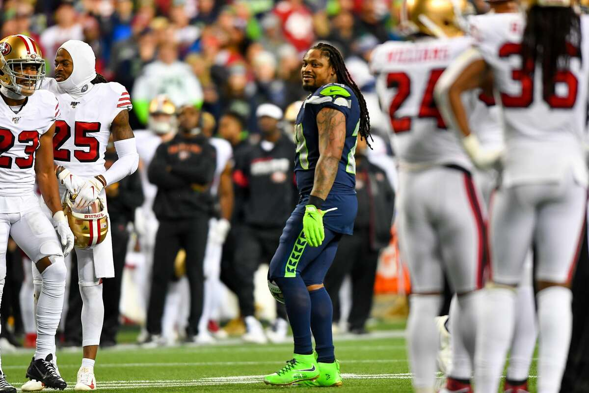 SEATTLE, WASHINGTON - DECEMBER 29: Marshawn Lynch #24 of the Seattle Seahawks, center, is all smiles after chatting with Richard Sherman #25 and other San Francisco 49ers during a break in the action at CenturyLink Field on December 29, 2019 in Seattle, Washington. The San Francisco 49ers top the Seattle Seahawks 26-21. (Photo by Alika Jenner/Getty Images)