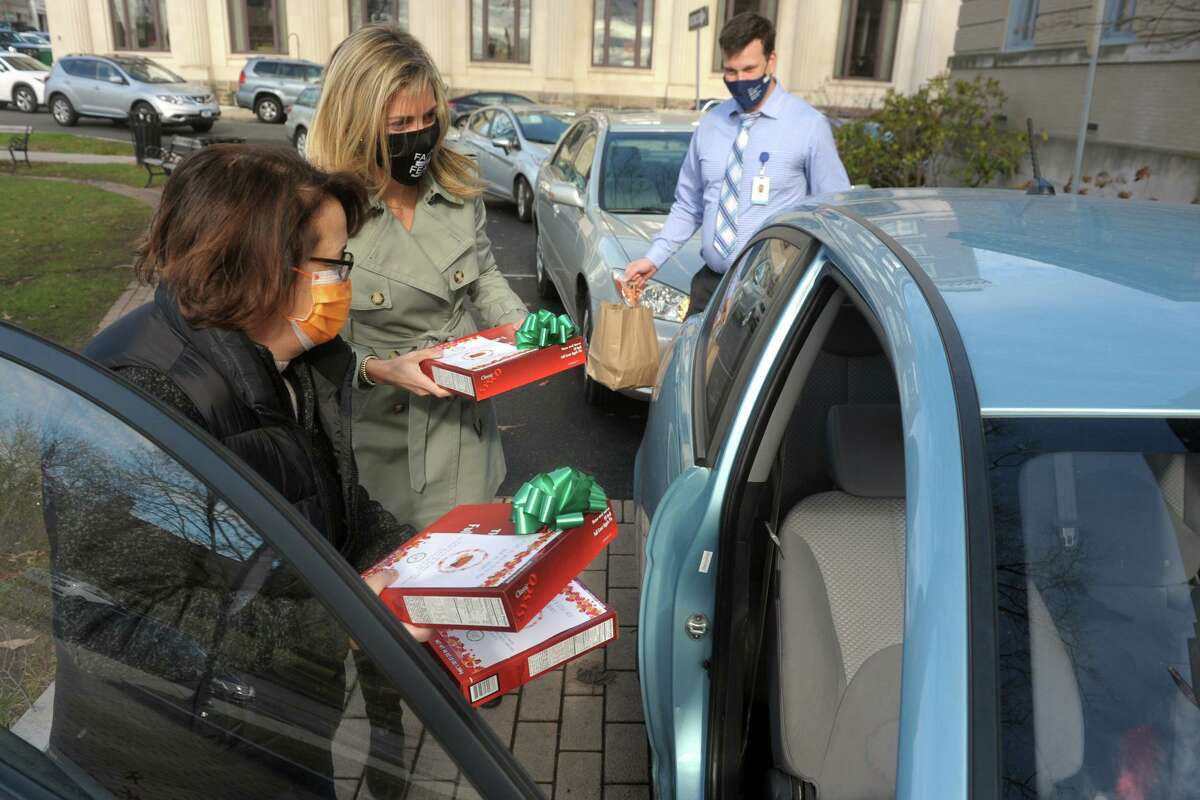 From left, Laurie Pensiero, Heather Keane and Gino Pirri deliver boxed pies and bagged Thanksgiving meals to a waiting car during the drive-thru lunch in front of the Greenwich Senior Center, in Greenwich, Conn. Nov. 23, 2020.