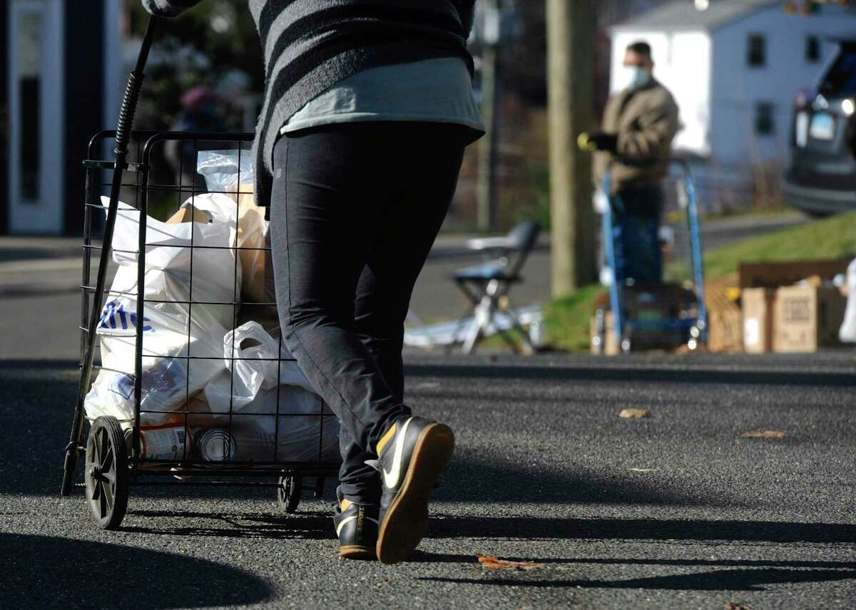 A client leaves the Daily Bread Food Pantry with three bags of food, including a turkey, on Tuesday morning, November 24, 2020, in Danbury, Conn. The pantry distributed about 200 turkeys and other food for Thanksgiving.