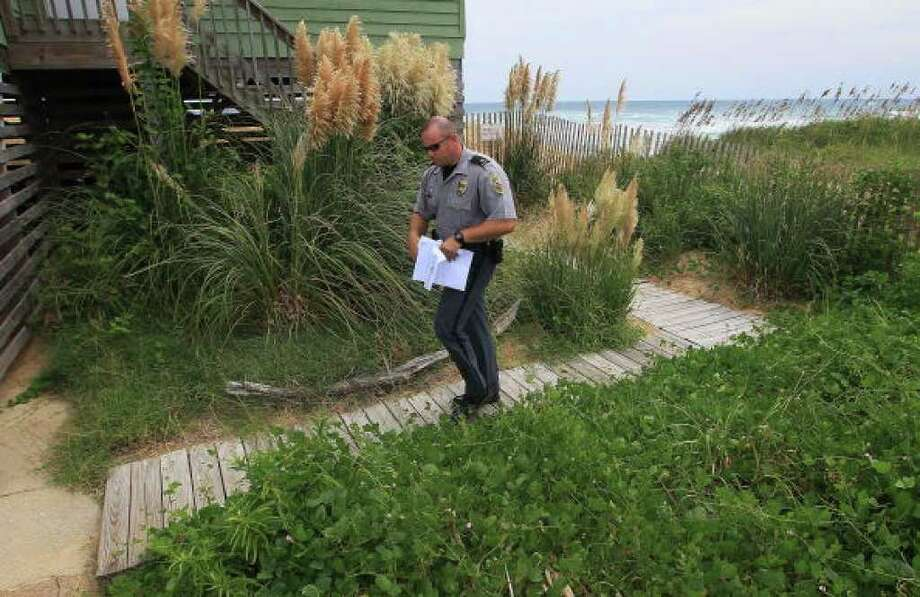 KITTY HAWK, NC - SEPTEMBER 02: A Kitty Hawk police officer delivers mandatory evacuation notices September 2, 2010 in Kitty Hawk, North Carolina. A mandatory evacuation notice has been issued for Dare County as Hurricane Earl, which is expected to pass the Outer Banks of North Carolina late Thursday night into Friday morning, approaches.  (Photo by Mark Wilson/Getty Images) Photo: Mark Wilson, Getty Images / Getty Images