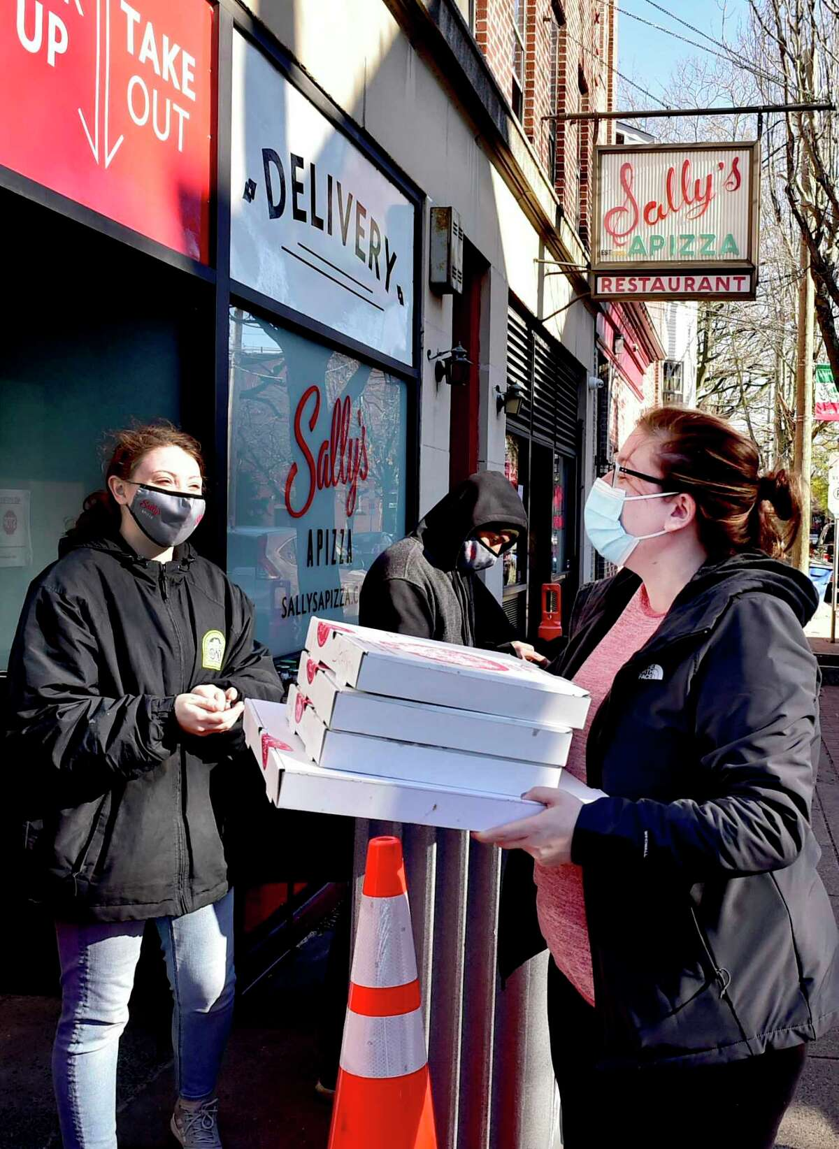 Katie Coland, a Sally's Apizza employee, left, serves a free takeout pizza to Bridgeport Hospital critical care nurse Jessica Wojiski, right, as the famous New Haven pizzeria offered free pizza to medical personnel Nov. 24, 2020.