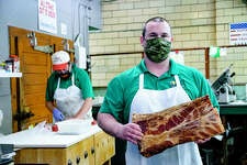 Kyle Smith poses with a dry-aged and smoked slab of bacon as Russ Martin cuts meat behind him Friday afternoon at Goshen Butcher Shop in Edwardsville.