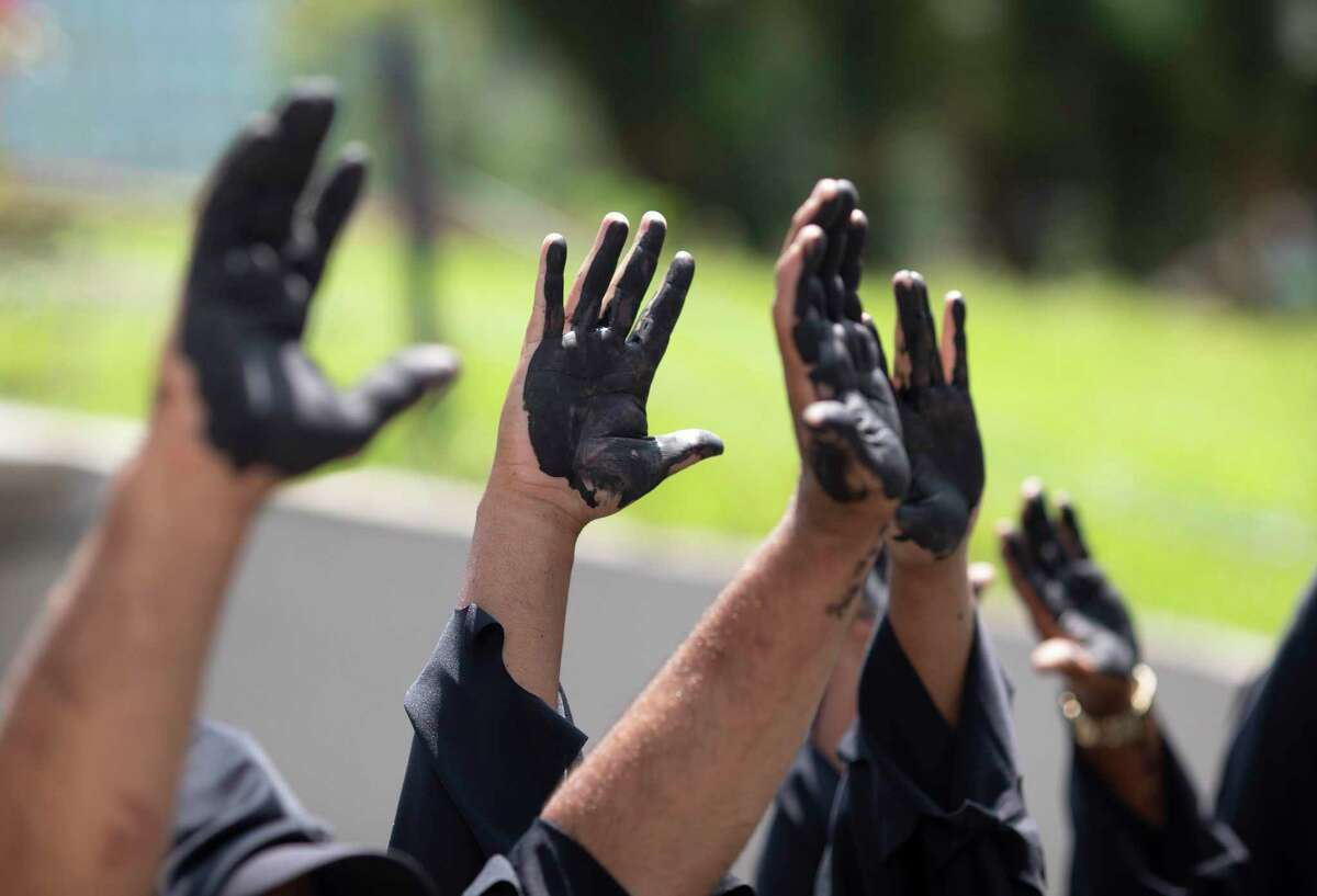 Demonstrators hold up their hands covered with mock oil outside the state-owned development bank BNDES in Rio de Janeiro, Brazil, Thursday, Nov. 12, 2020. The protest calls on the bank to stop financing oil, gas and coal-related projects and to redirect its resources to help deal with the climate crisis. (AP Photo/Silvia Izquierdo)
