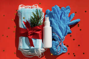 Hygienic face masks antibacterial gel and medical gloves as a gift with a red ribbon, Christmas and New Year 2021 decor on a red background. Holidays self-isolation and coronavirus concept   The pandemic rages on, but so does holiday shopping season. Here's what retail workers want you to know before Black Friday.