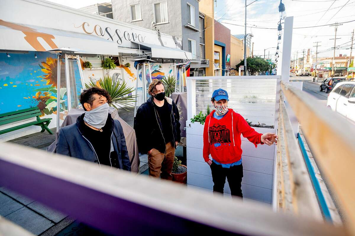 """Alec Hawley (right) speaks with contractor Mike Tinnea and artist Pablo """"Raiz"""" Arroyo inside the parklet they created for Cassava in San Francisco."""