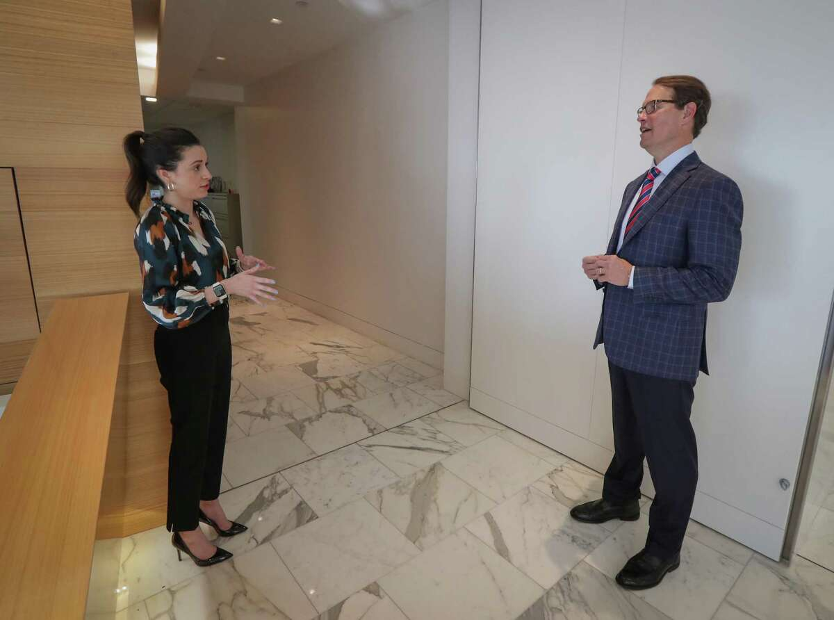 Kaitlyn Harp (left), executive assistant to the CEO / CFO talks to Larry Heard, CEO of the Transwestern commercial real estate firm Wednesday, Nov. 18, 2020, in Houston.