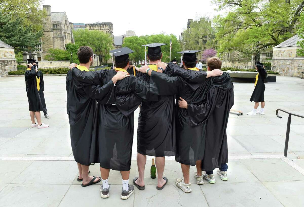 Yale University graduates pose for photographs on Cross Campus in New Haven on what would have been their commencement on May 18, 2020. Yale University President Peter Salovey delivered an address and conferred degrees via YouTube.