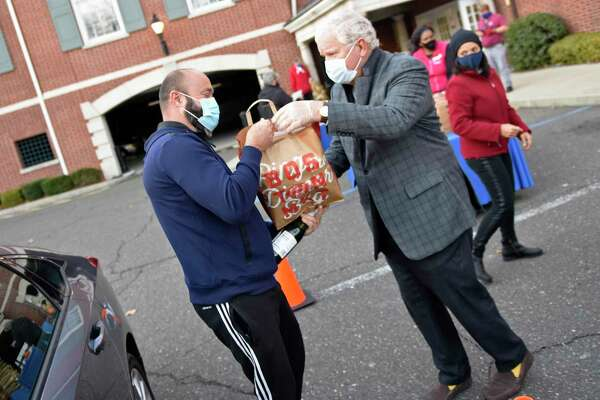 Greenwich's Antonio Silva, left, accepts a Thanksgiving meal from Boys & Girls Club of Greenwich board member Bill Farrell during the Thanksgiving meal distribution at the Boys & Girls Club in Greenwich, Conn. Tuesday, Nov. 24, 2020. Instead of the usual buffet-style dinner for club kids, this year the Boys & Girls Club handed out Thanksgiving dinners fit to feed a family of six. More than 100 club families were fed full Thanksgiving meals of a rotisserie chicken, cornbread, stuffing, mashed potatoes, pies, and sparkling wine.